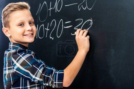 Photo pour Sourire le garçon écrit exemple math sur tableau noir avec craie et regardant la caméra - image libre de droit