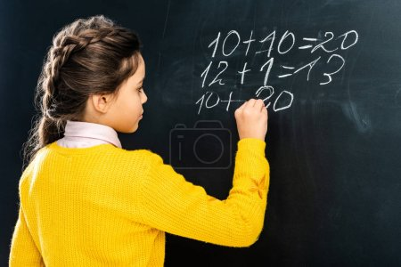 Photo for Schoolgirl in yellow sweater writing on blackboard with chalk - Royalty Free Image