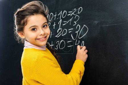 Photo pour Souriant écolière écriture sur tableau noir avec craie et regardant la caméra - image libre de droit
