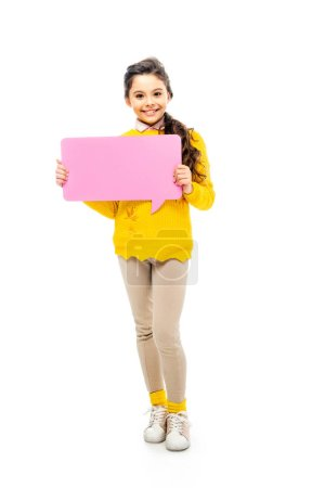 happy schoolgirl in yellow sweater holding pink speech bubble and looking at camera isolated on white