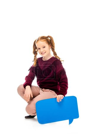 smiling schoolgirl sitting on hunkers, holding speech bubble and looking at camera isolated on white