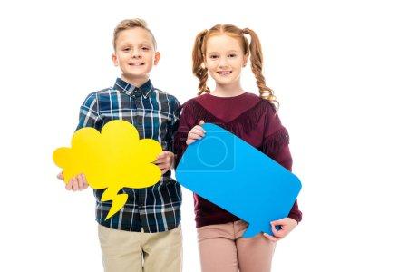 Foto de Sonriendo a los niños de pie, sosteniendo las burbujas del discurso multicolor y mirando a cámara aislada en blanco - Imagen libre de derechos