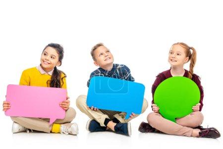 Photo pour Enfants gais assis et tenant des bulles de parole multicolores isolés sur blanc - image libre de droit