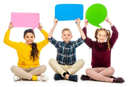 Photo for Smiling kids sitting and holding speech bubbles over heads isolated on white - Royalty Free Image