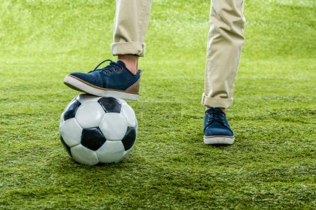 Photo for Cropped view of boy with leg standing on soccer ball on lawn - Royalty Free Image