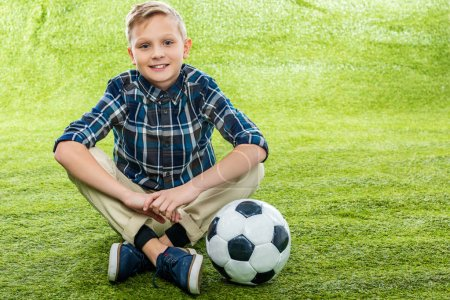 Photo for Smiling boy sitting on lawn near soccer ball and looking at camera - Royalty Free Image