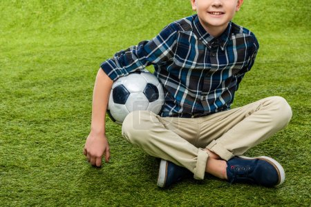 Photo for Cropped view of smiling boy holding soccer ball and sitting on lawn - Royalty Free Image