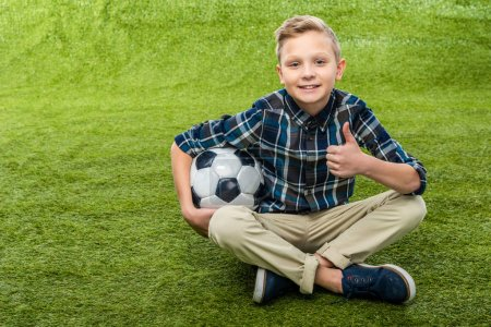 Photo for Smiling boy holding soccer ball, looking at camera and showing thumb up on lawn - Royalty Free Image
