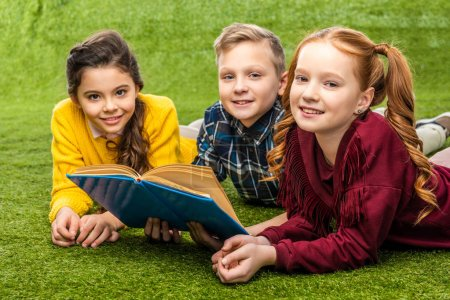 cute preteen schoolkids lying on green lawn, holding book and looking at camera