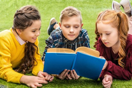 Photo for Cute kids lying on lawn and reading book - Royalty Free Image