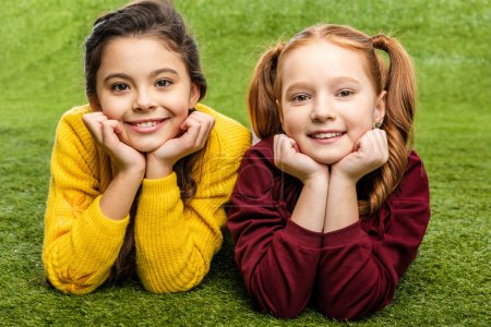 Photo for Smiling schoolgirls lying on lawn and looking at camera - Royalty Free Image