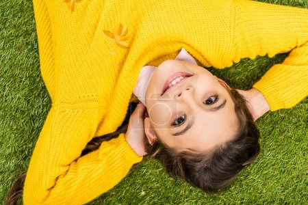 top view of smiling schoolgirl in yellow sweater with hands on head looking at camera and lying on lawn