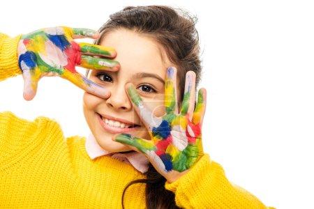 Photo pour Gros plan vue d'écolière mignon dans le chandail jaune souriant, regardant la caméra et montrant les mains peintes dans les peintures colorées isolés sur blanc - image libre de droit