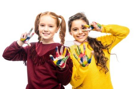 Photo pour Écolières souriantes montrant des signes de paix avec les mains peintes dans des peintures colorées et en regardant la caméra isolée sur blanc - image libre de droit