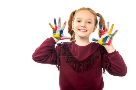 Photo for Smiling schoolgirl looking at camera and showing hands painted in colorful paints isolated on white - Royalty Free Image