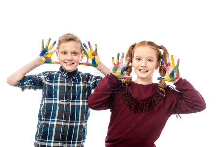 cute schoolchildren looking at camera and showing hands painted in colorful paints isolated on white