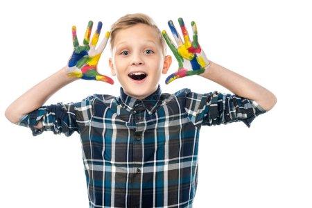 Photo pour Garçon avec la bouche ouverte montrant les mains peintes dans des peintures colorées et regardant la caméra isolée sur blanc - image libre de droit