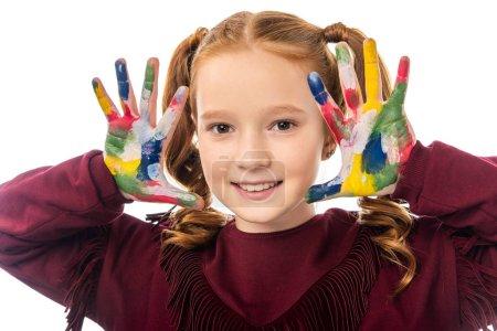 Photo pour Vue rapprochée de l'écolière mignonne regardant la caméra et montrant les mains peintes dans des peintures colorées isolées sur blanc - image libre de droit