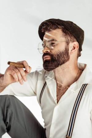 thoughtful bearded man in glasses and cap holding cigar on white background