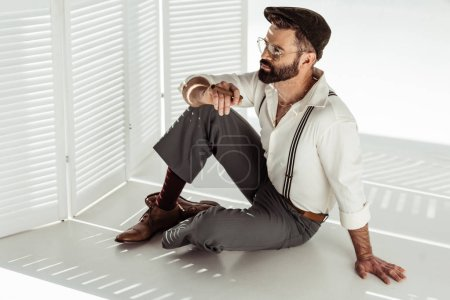 thoughtful bearded man in glasses and cap sitting on floor near room divider and holding cigar