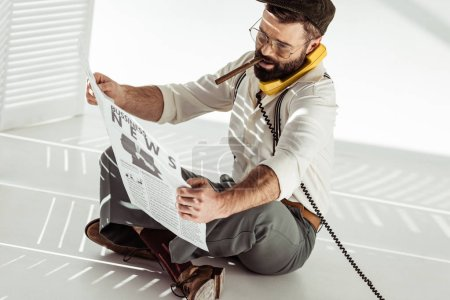 handsome bearded man sitting on floor, talking on phone, smoking cigar and reading business newspaper
