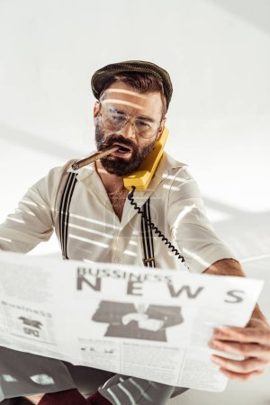 Photo for Handsome bearded man in glasses talking on phone, smoking cigar and reading business newspaper - Royalty Free Image