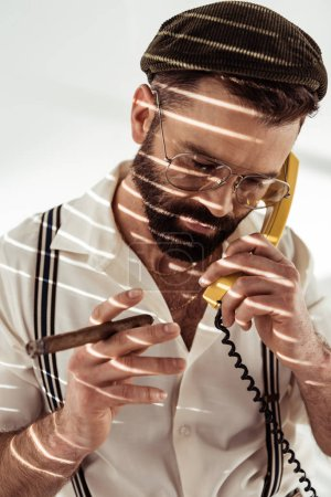 handsome bearded man talking on phone and holding cigar