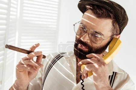 bearded man in glasses and cap talking on phone and holding cigar