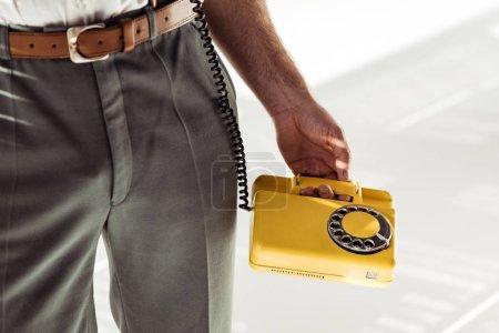 Photo pour Recadrée de l'homme tenue rétro téléphone jaune sur fond blanc - image libre de droit