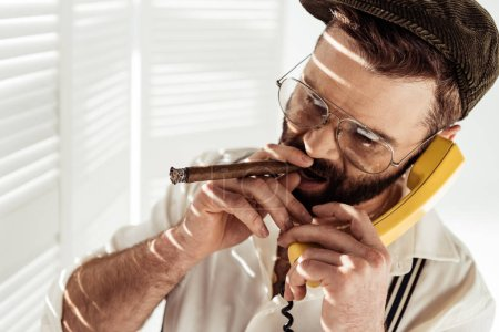 Photo for Handsome bearded man in glasses talking on phone and smoking cigar - Royalty Free Image