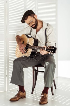 Photo for Handsome bearded musician in cap sitting on chair and playing acoustic guitar - Royalty Free Image
