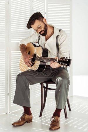 Photo pour Beau musicien barbu à capuchon, assis sur la chaise et jouer de la guitare acoustique - image libre de droit