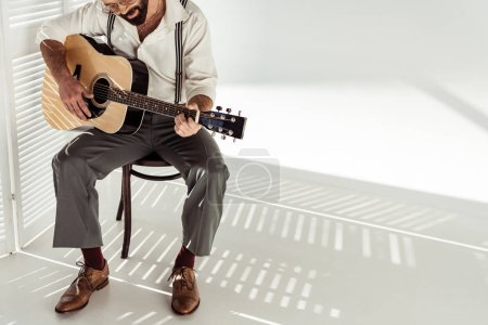Photo for Bearded man in glasses sitting on chair and playing acoustic guitar near white room divider - Royalty Free Image