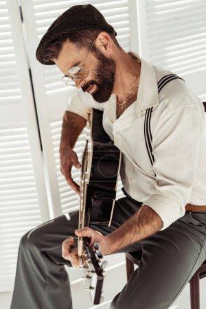 Photo pour Bel homme barbu assis sur la chaise et jouer de la guitare acoustique près de paravent à la salle - image libre de droit