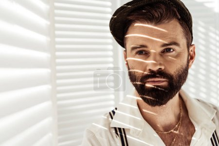 Photo for Handsome bearded man in cap near white room divider - Royalty Free Image