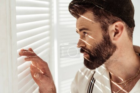 side view of handsome bearded man in cap looking through white room divider