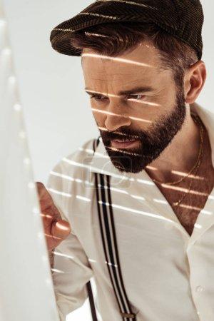 Photo pour Bel homme barbu regardant à travers le diviseur de pièce - image libre de droit