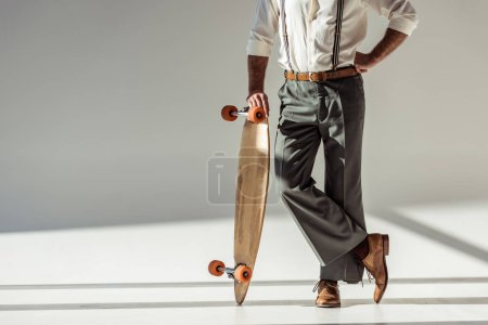 cropped view of stylish man holding longboard on grey background