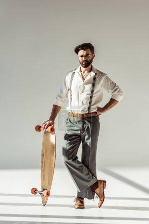 Photo pour Bel homme barbu tenant longboard et regardant la caméra sur fond gris - image libre de droit