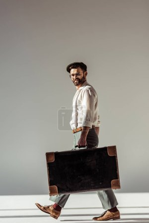 Photo for Handsome bearded man in glasses and cap walking with retro suitcase and looking at camera on grey background - Royalty Free Image