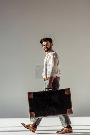 Photo pour Bel homme barbu en lunettes et une casquette à pied avec valise rétro et regardant la caméra sur fond gris - image libre de droit