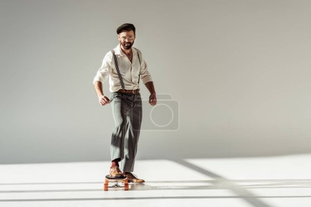 Photo pour Bel homme barbu chevauchant longboard et regardant la caméra sur fond gris - image libre de droit