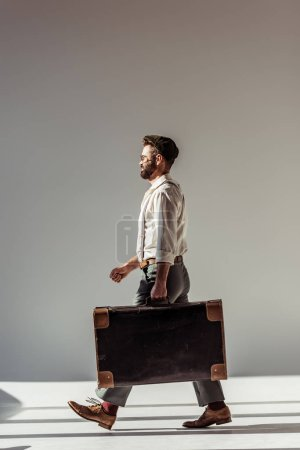 Photo for Handsome man in glasses and cap walking with retro suitcase on grey background - Royalty Free Image
