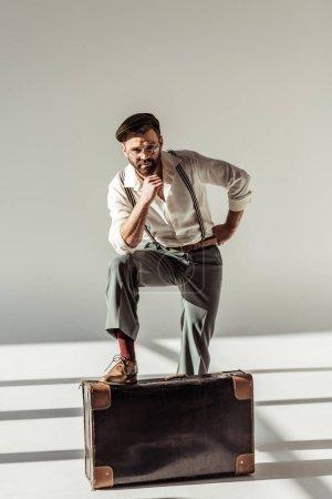 Photo pour Bel homme barbu près de valise rétro et regardant la caméra sur fond gris - image libre de droit
