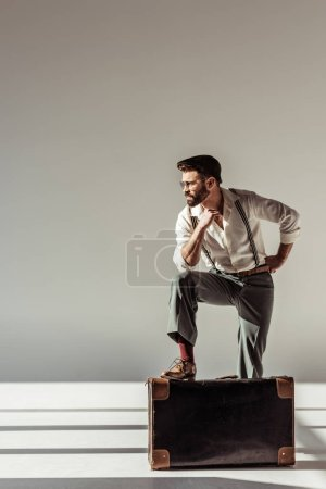 Photo for Handsome bearded man near retro suitcase on grey background - Royalty Free Image