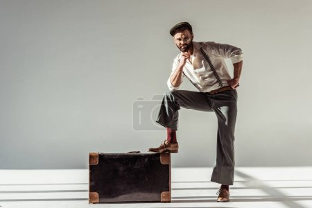 Photo for Handsome man in glasses and cap near retro suitcase looking at camera on grey background - Royalty Free Image