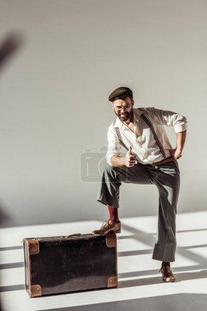 Photo pour Homme barbu avec valise vintage montrant le pouce vers le haut et regardant la caméra sur fond gris - image libre de droit