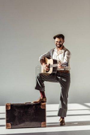 Photo pour Souriant barbu au cap près de valise vintage, jouer de la guitare acoustique et regardant la caméra sur fond gris - image libre de droit