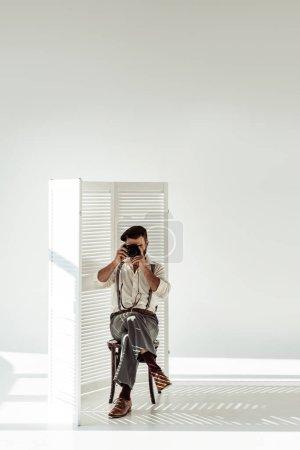Foto de Hombre con barba sentado en silla cerca del tabique y tomar fotografías con cámara vintage - Imagen libre de derechos