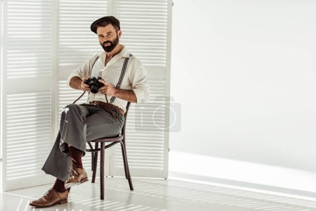 bearded stylish man sitting on chair with vintage film camera